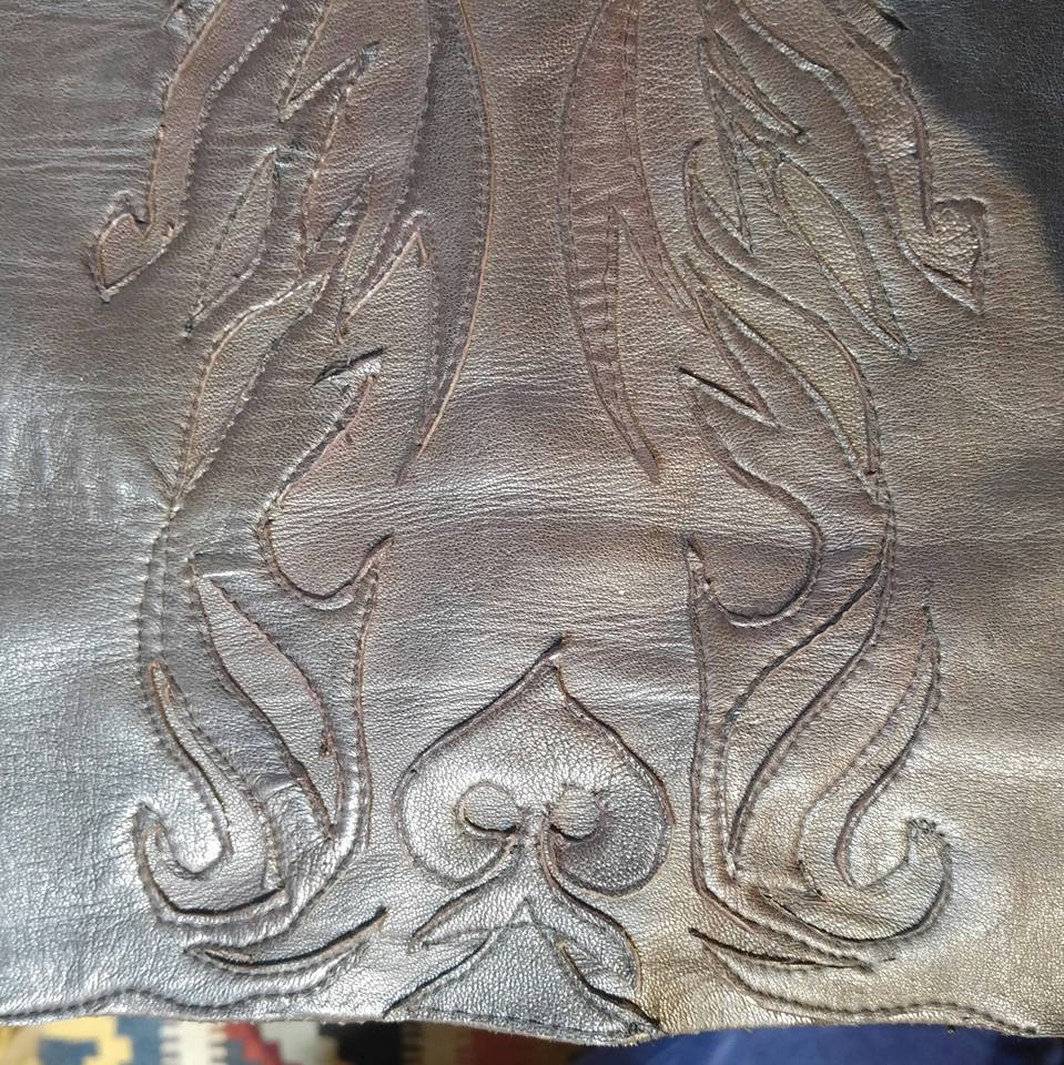 Applique can be used to use leftover material as well as decorate. This leather skirt was made from a pair of second hand leather trousers. The leftover material was used as decoration and to reduce waste.